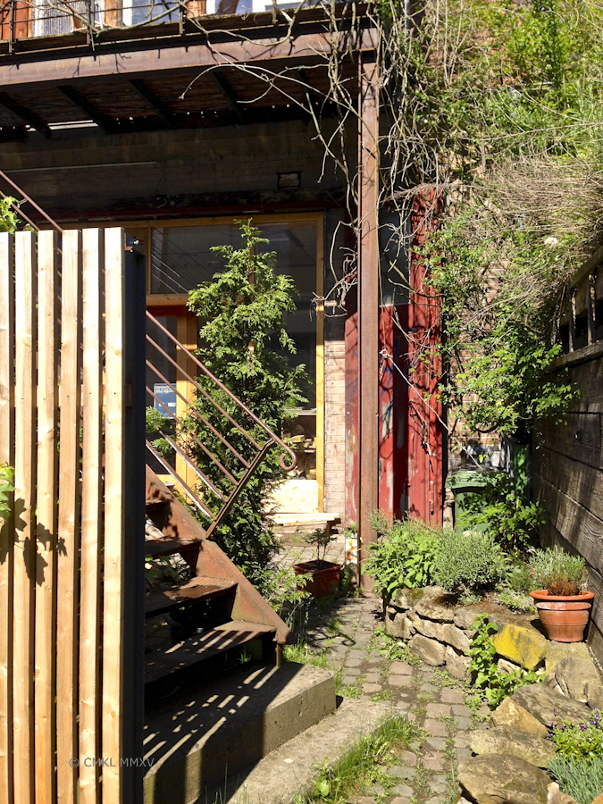 This romantic garden includs a set of red former mashine shop doors
