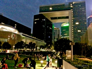Family picnic into the night and the looming presence of a gigantic government building complex.