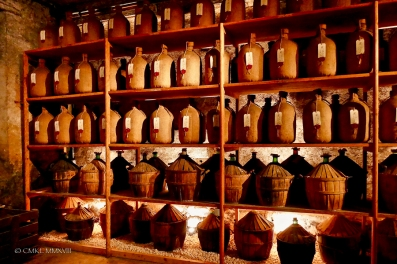 These glass containers are wrapped in burlap or encased in wood to protect the cognac within from light degradation.
