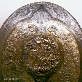 "Copy of the famed ""Milton Shield"", a 1866 Leonard Morel-Labeuil damascened steel shield [87x67cm] with chased silver inlays, detail. The shield shows scenes from Milton's Paradise Lost. In the center medallion the Archangel Raphael is telling Adam & Ev of Lucifer's rebellion."