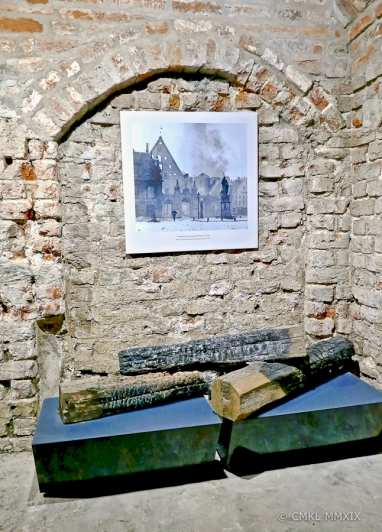 Charred beams from the original building. Above a photo of the 1948 Soviet detonation of the ruin of the House of the Blackheads, following its bombing in 1941.