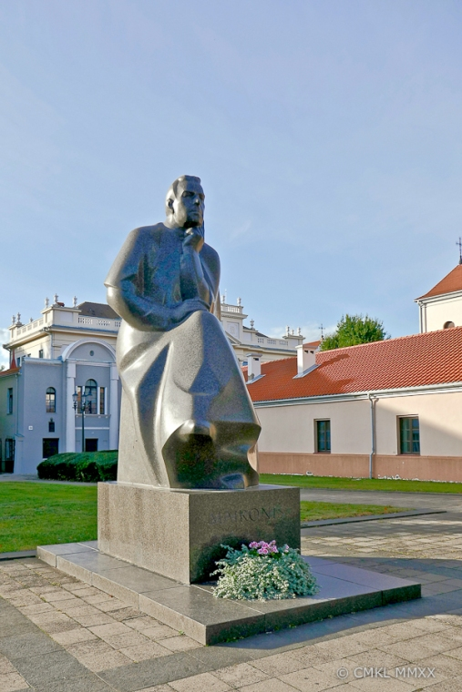 Behind the monument in blue-grey, the guesthouse of the Archdiocese, in yellow the Kaunas Theological Seminary.